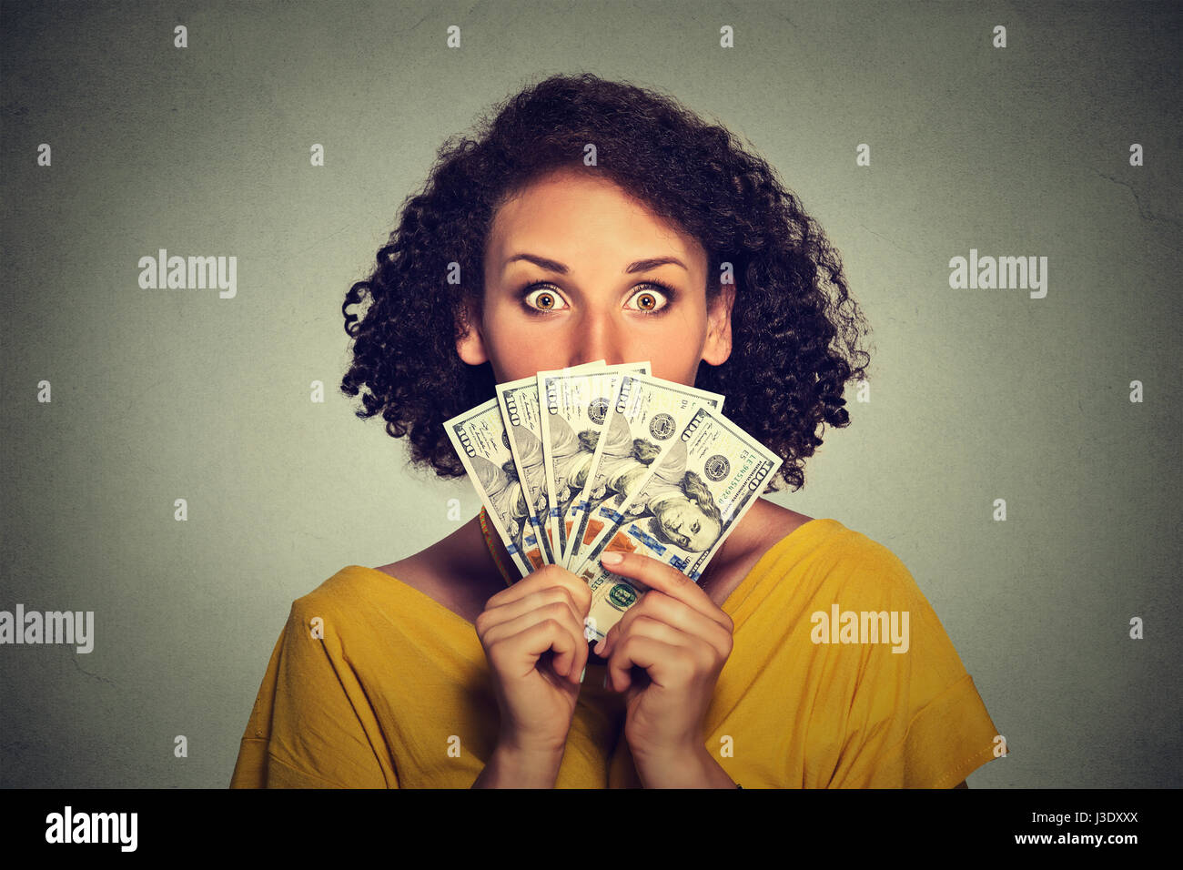 Scared looking woman hiding picking through dollar banknotes - Stock Image