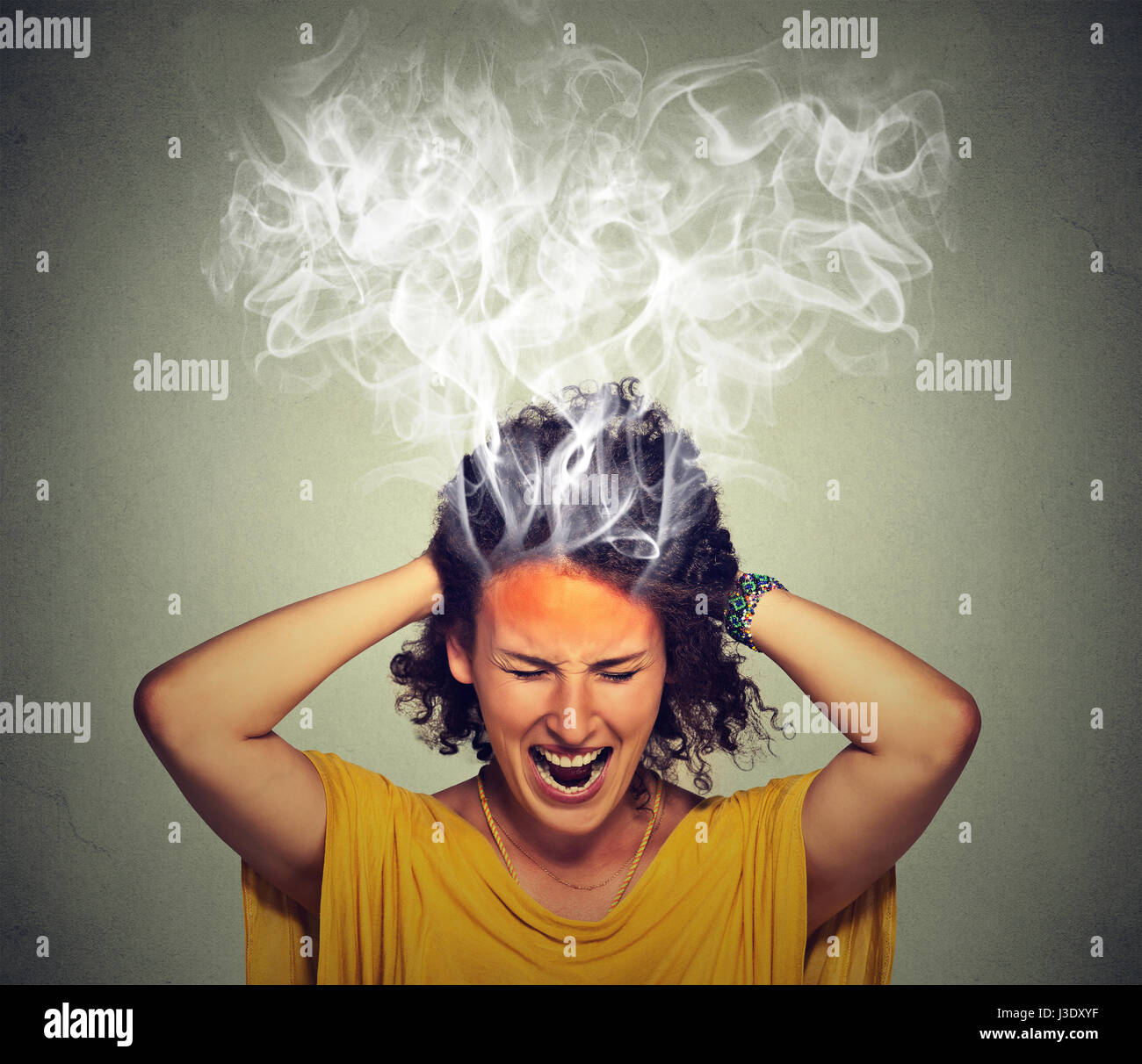 Portrait young stressed woman screaming frustrated thinking too hard steam coming out up of head isolated on grey - Stock Image