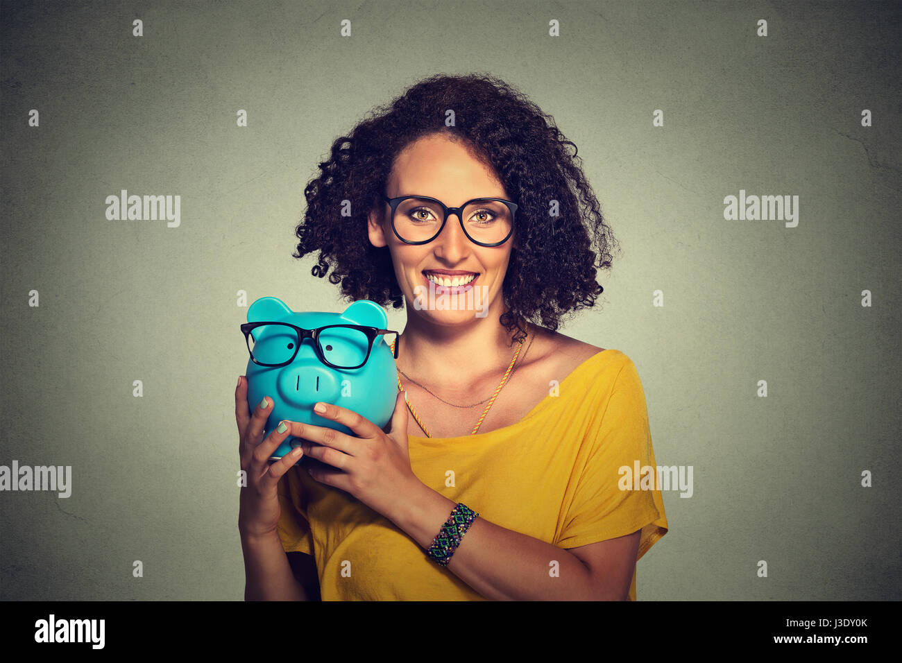 Save money on glasses eyewear concept. Happy woman excited over savings on buying glasses. Piggybank and woman wearing - Stock Image
