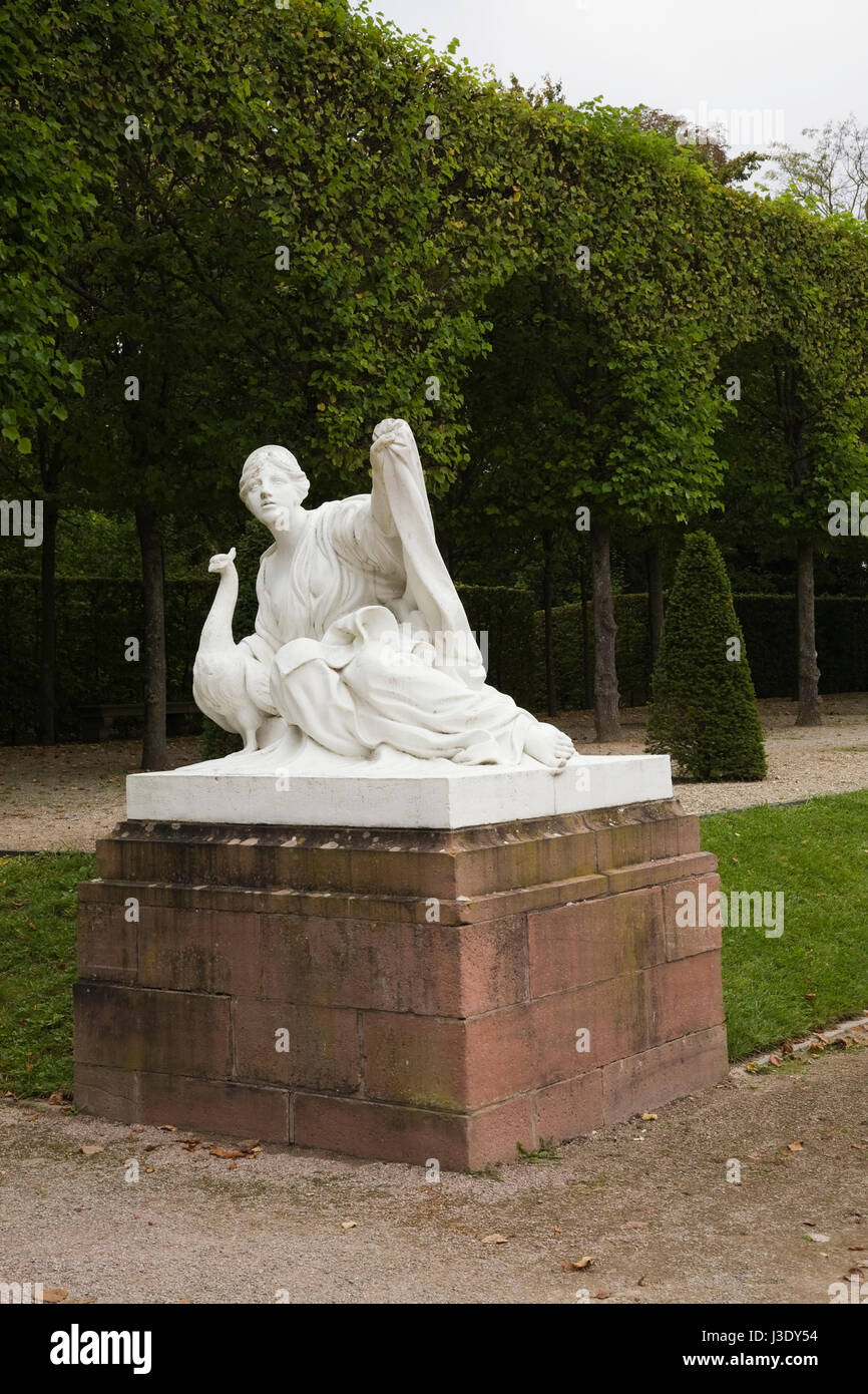 Peacock and young male sculpture with topiary in the Schwetzingen palace garden in late summer, Schwetzingen, Germany, - Stock Image
