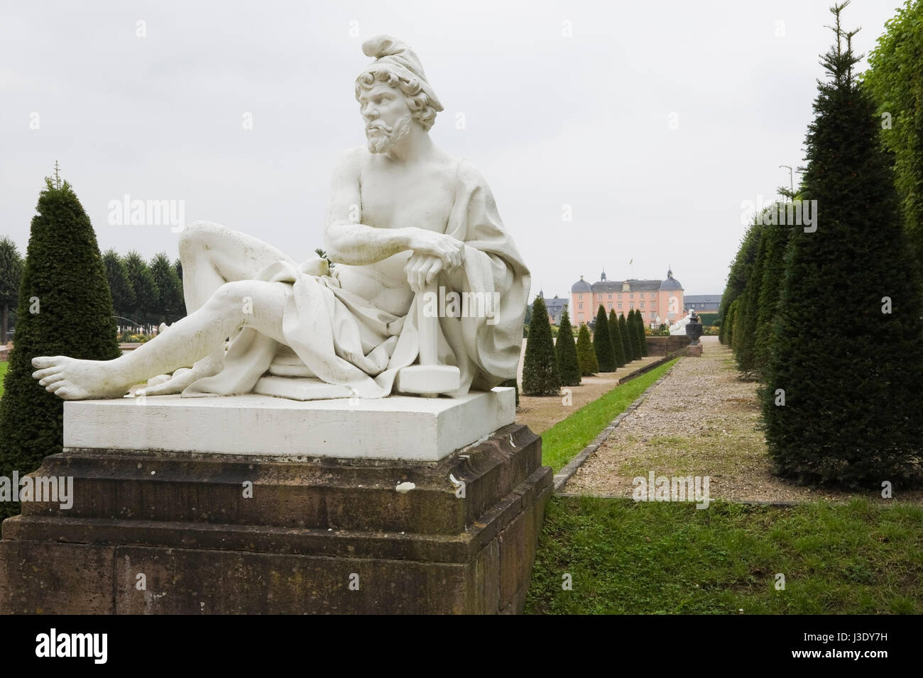 Older man sculpture and topiary in the Schwetzingen palace garden in late summer, Schwetzingen, Germany, Europe. - Stock Image