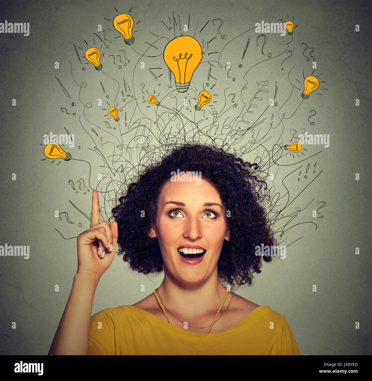 Closeup excited woman with many ideas light bulbs above head looking up pointing finger up isolated on gray wall - Stock Image