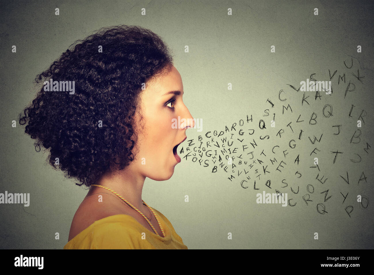 Woman talking with alphabet letters coming out of her mouth. Communication, information, intelligence concept - Stock Image