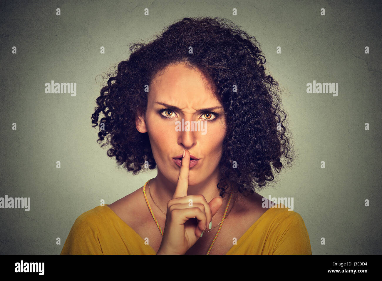 Portrait of young beautiful woman with finger on lips isolated on gray wall background - Stock Image
