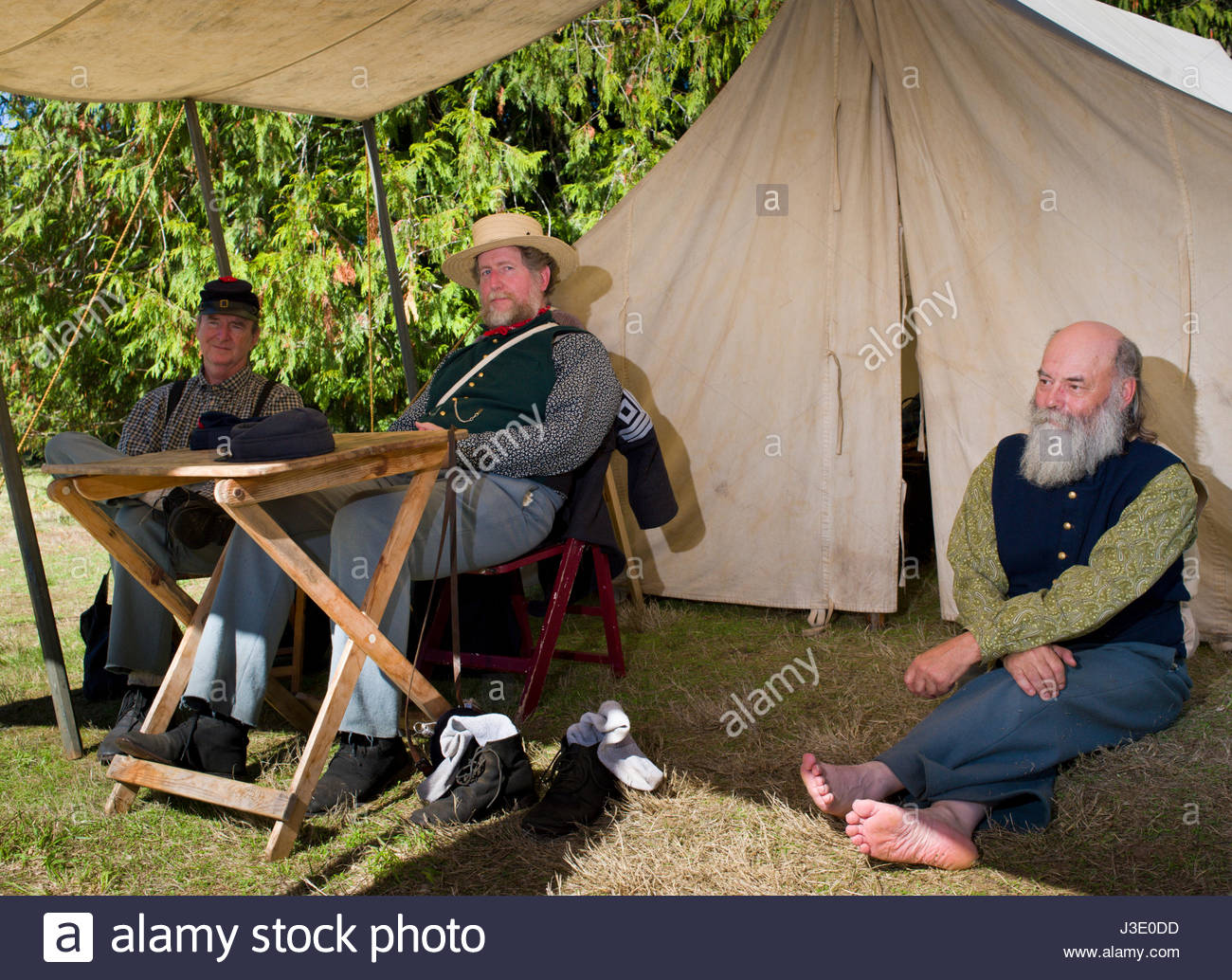 Three men sitting in the shade of a white canvas awning resting on a hot day at Civil War Reenactment, Milo McIver - Stock Image