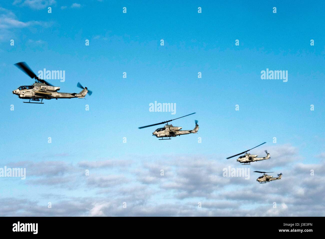Four USMC AH-1W Super Cobra attack helicopters fly in formation over Buckner Bay April 5, 2017 in the Pacific Ocean. - Stock Image