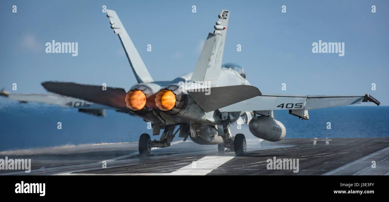 A USN F/A-18C Hornet jet fighter aircraft takes off from the flight deck aboard the USN Nimitz-class aircraft carrier - Stock Image