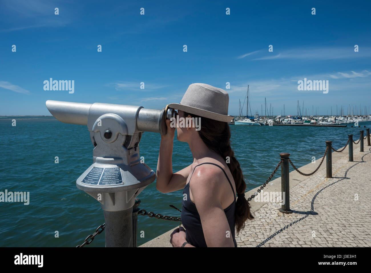 woman looking through a coin operated telescope on the seafront - Stock Image
