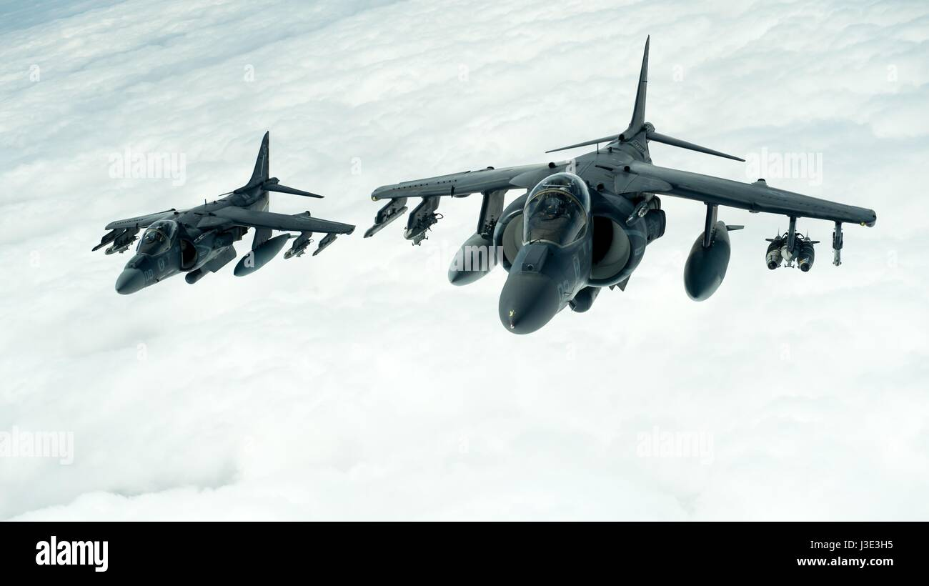 Two USMC AV-8B Harrier II ground-attack aircraft fly in formation during an Operation Inherent Resolve mission March - Stock Image