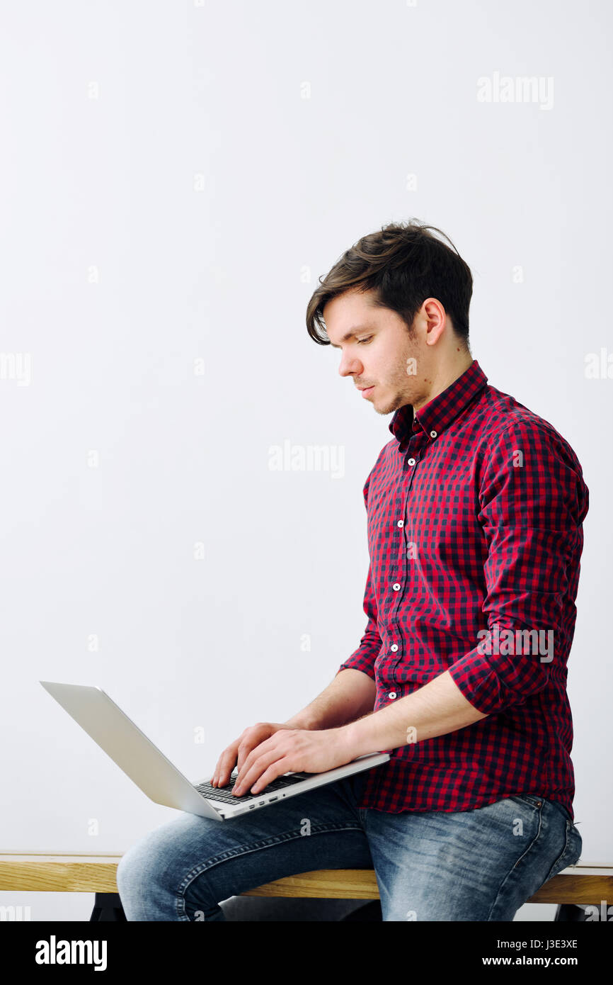 Man working on laptop sitting on desk in office. Young goal-oriented guy. The concept of a successful person - Stock Image