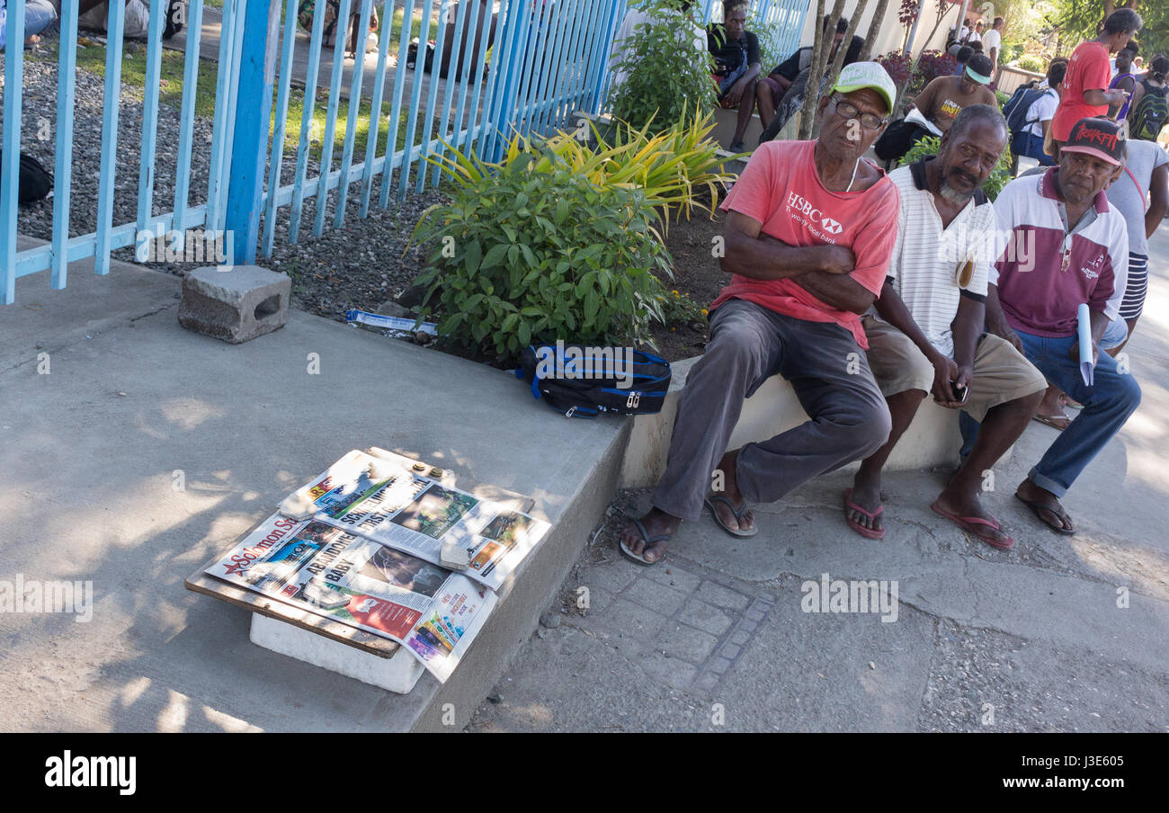 Honiara, Solomon Island - March 7th, 2017: A street vendor selling local newpapers from Solomon Island across the - Stock Image