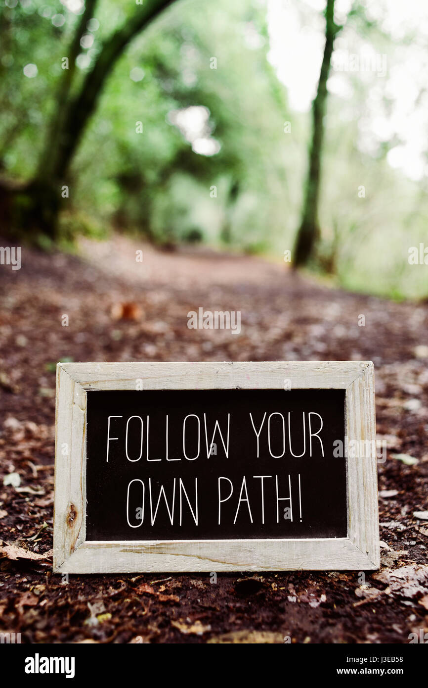closeup of a wooden-framed chalkboard with the text follow your own path written in it, placed on the ground in - Stock Image