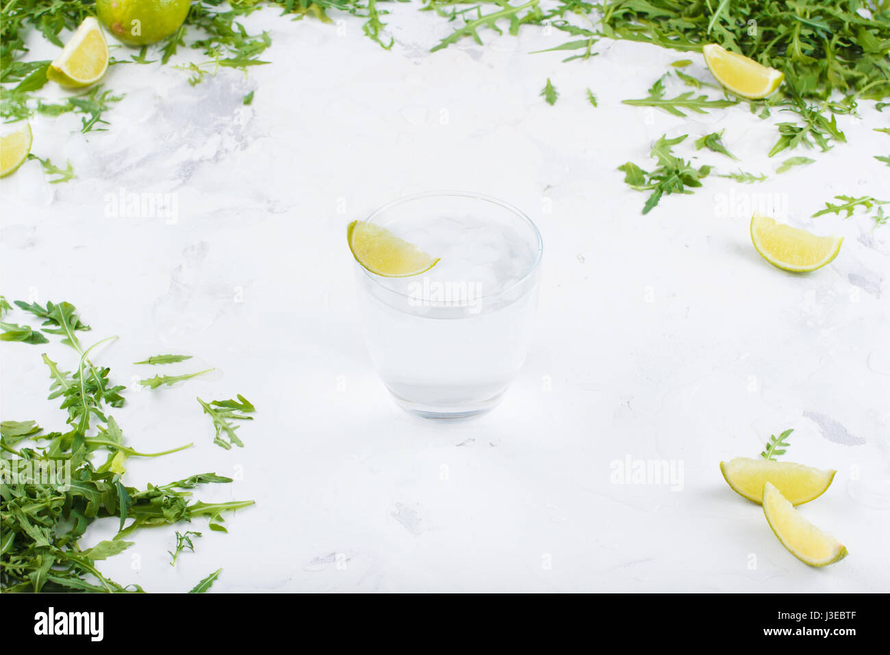 Fresh limes in the water on a white background. Greens and slices of lime in the background. A glass of water with - Stock Image