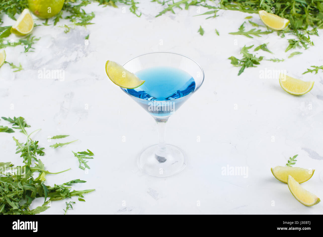A refreshing blue cocktail with lime in a martini glass on a white background. Cocktail on a background of greenery - Stock Image
