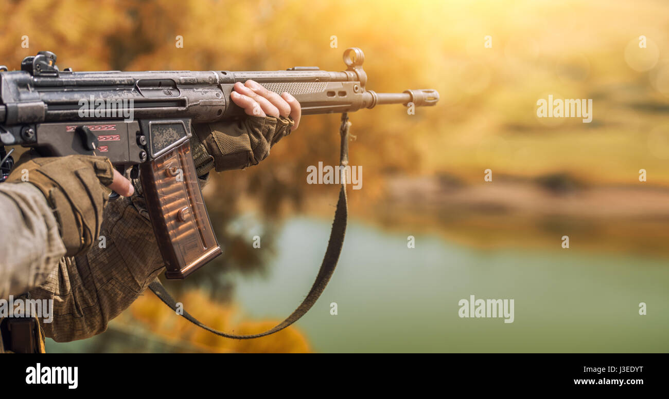 The soldier in camouflage and protective gloves, holding a gun. The zone of military operations. - Stock Image