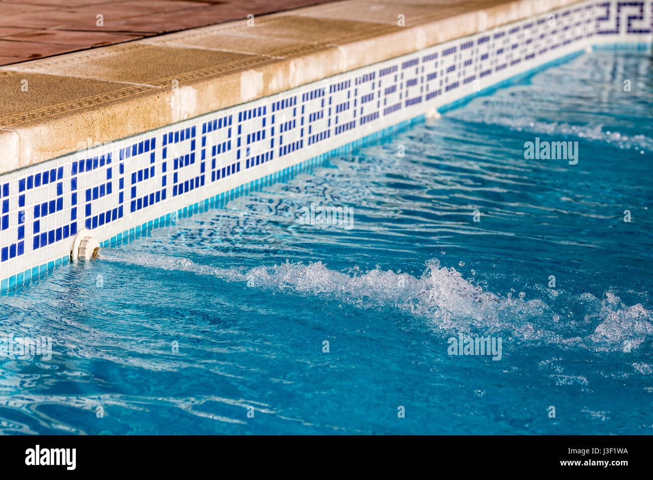 Water jets flowing into a swimming pool with blue tiles Stock Photo ...