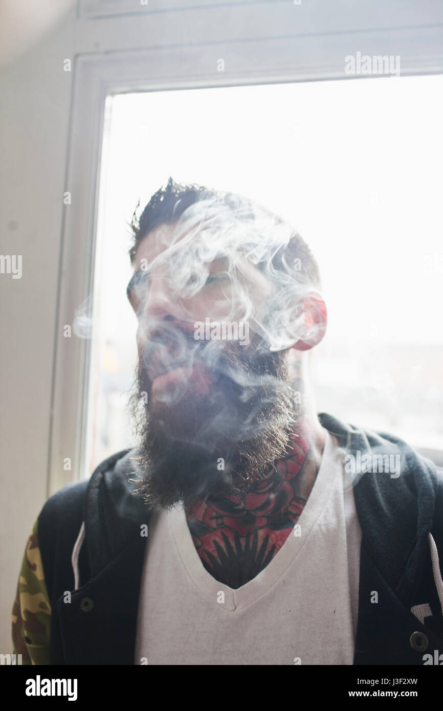 Young man smoking - Stock Image