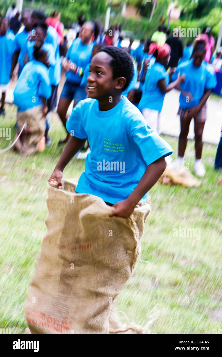 Miami Florida Little Haiti Range Park Back to School event Black boy sack race compete participate play game community - Stock Image