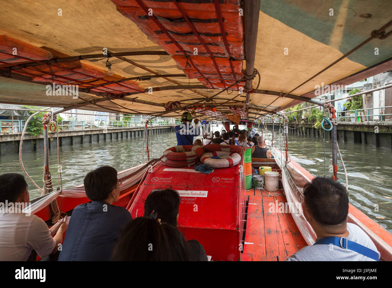 Several people on a khlong canal boat in Bangkok, Thailand. Stock Photo