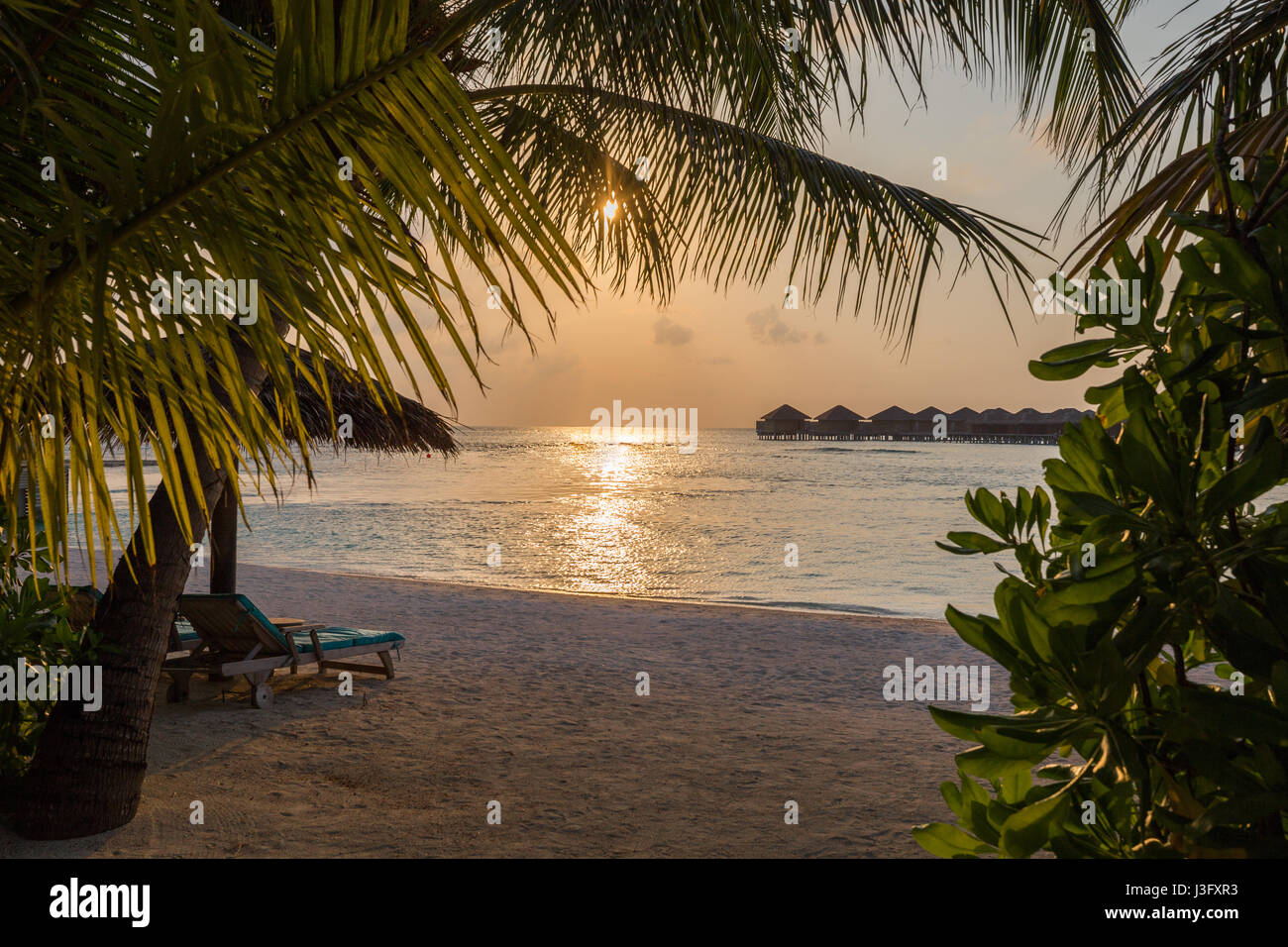Tropical Paradise Sunset Sunrise View of Over Water Bungalows with Orange Red Sky - Stock Image