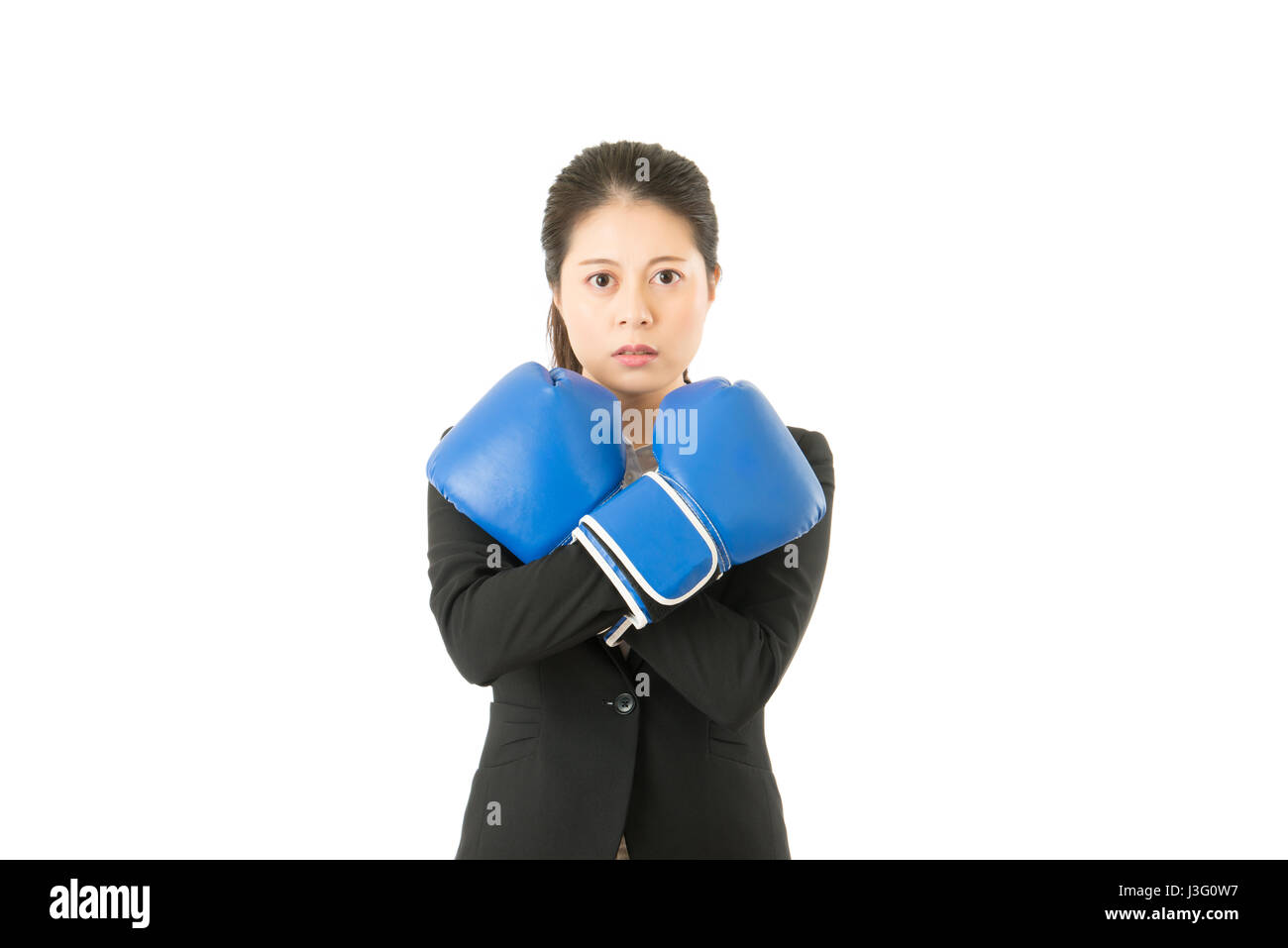 Business woman in boxing gloves cross arms defense from attack Stock