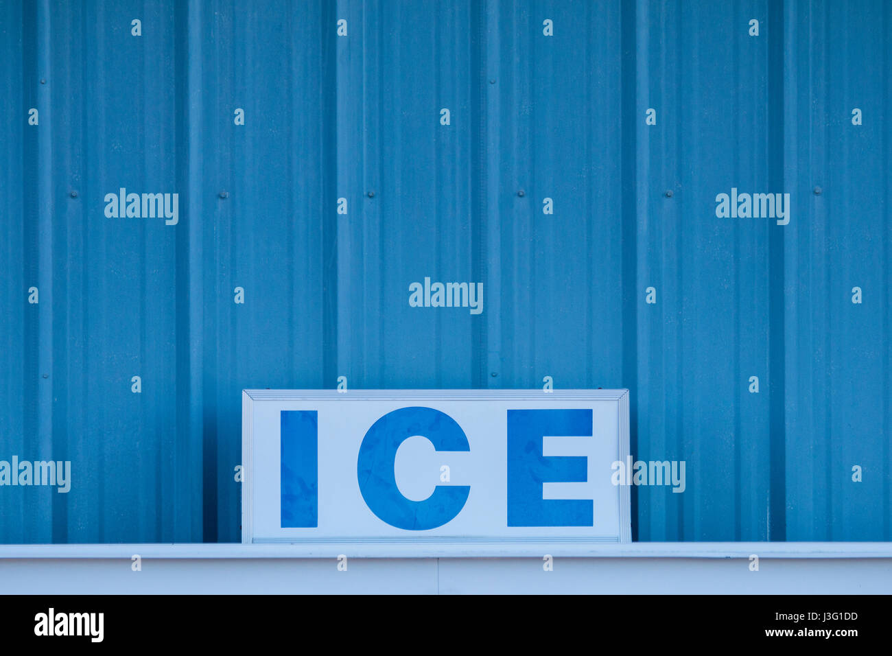 Word ICE in capital letters on sign in front of cold blue metal wall - Stock Image