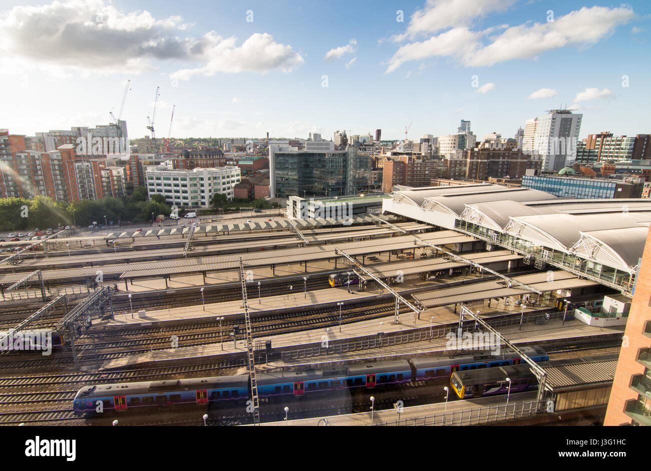 Leeds, England - June 28, 2015: Looking across waiting trains at the platforms of Leeds Railway Station to the skyline - Stock Image