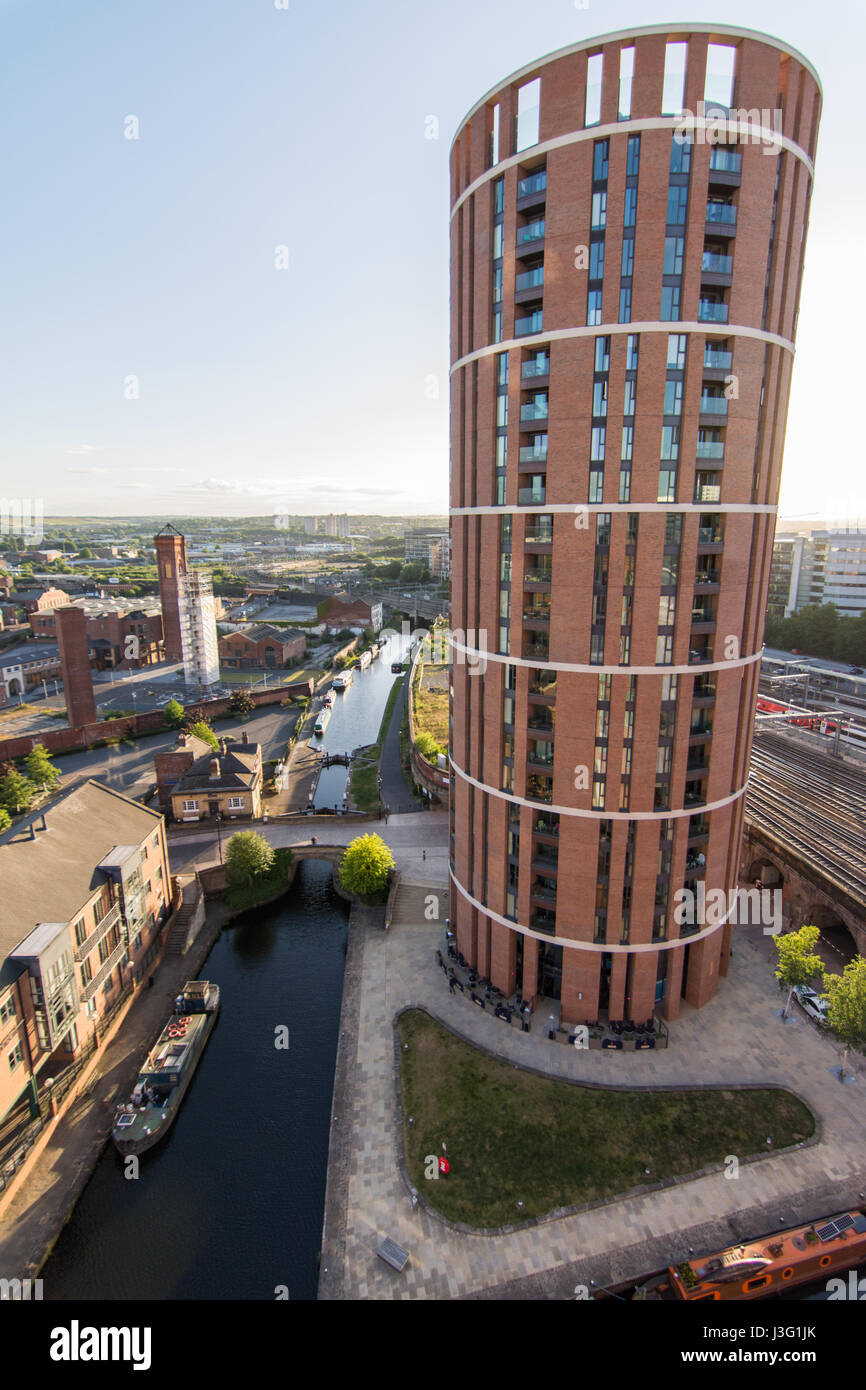 Candle House, a round tower apartment building, rises beside Leeds Railway Station and the Leeds and Liverpool Canal - Stock Image