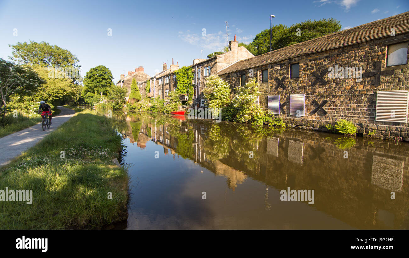 Leeds, England - June 30, 2015: A cyclist rides on the towpath alongside the Leeds and Liverpool Canal at Rodley - Stock Image