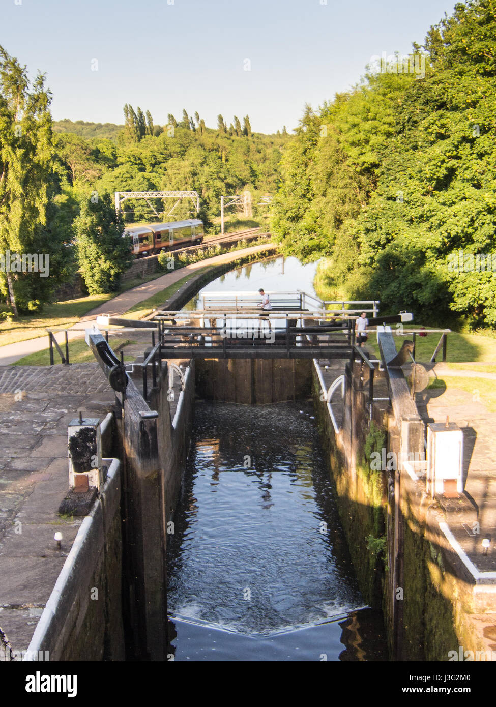 A Northern Rail passenger train on the Airedale Line railway passes the flight of staircase locks at Kirkstall Forge - Stock Image