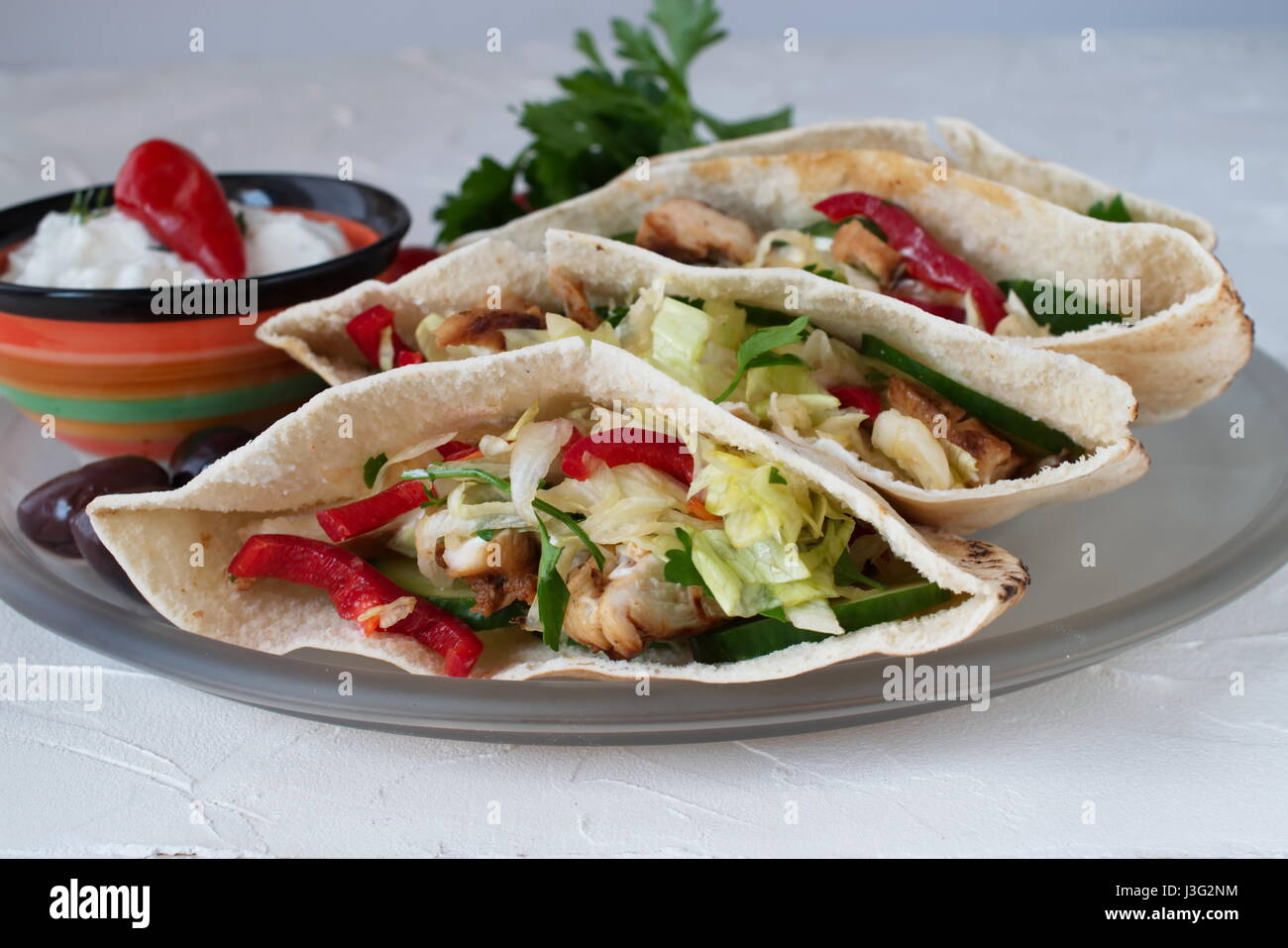 Pita filled with grilled chicken fillet, fresh salad, cucumber, sweet paprika, onion and yoghurt sauce on a white - Stock Image