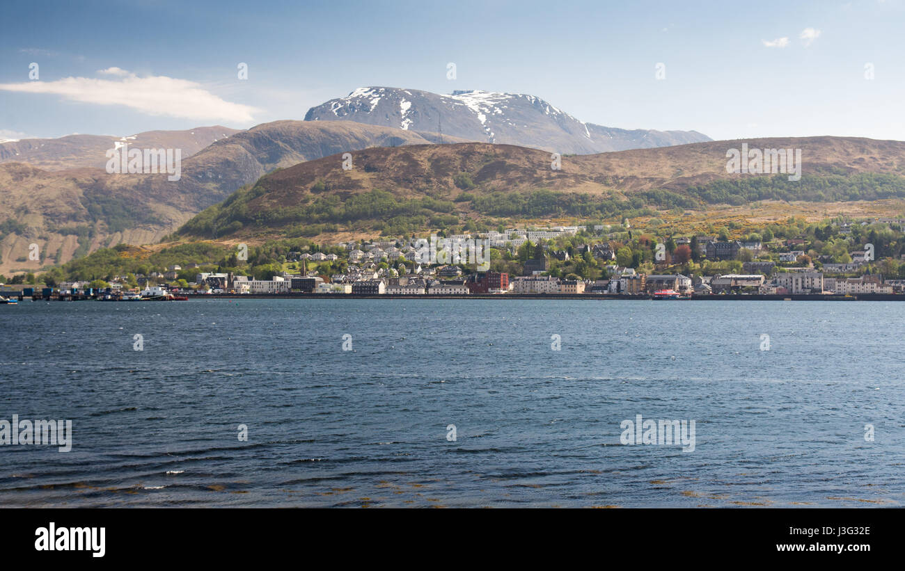 Ben Nevis, the UK's highest mountain, rises behind Loch Linnhe, with the town of Fort William on the sea shore. Stock Photo
