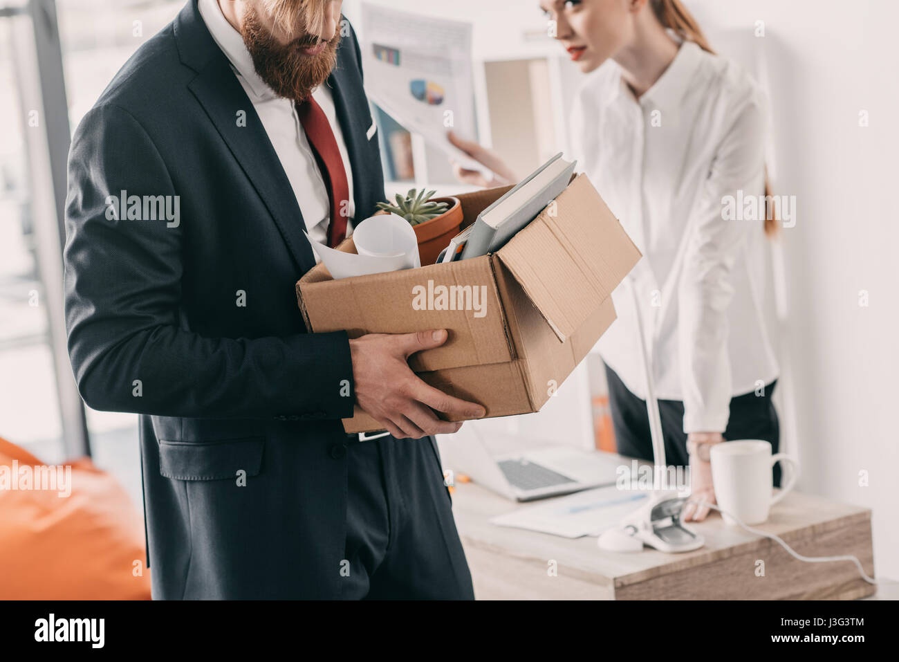 Young upset fired businessman with cardboard box and businesswoman in office - Stock Image