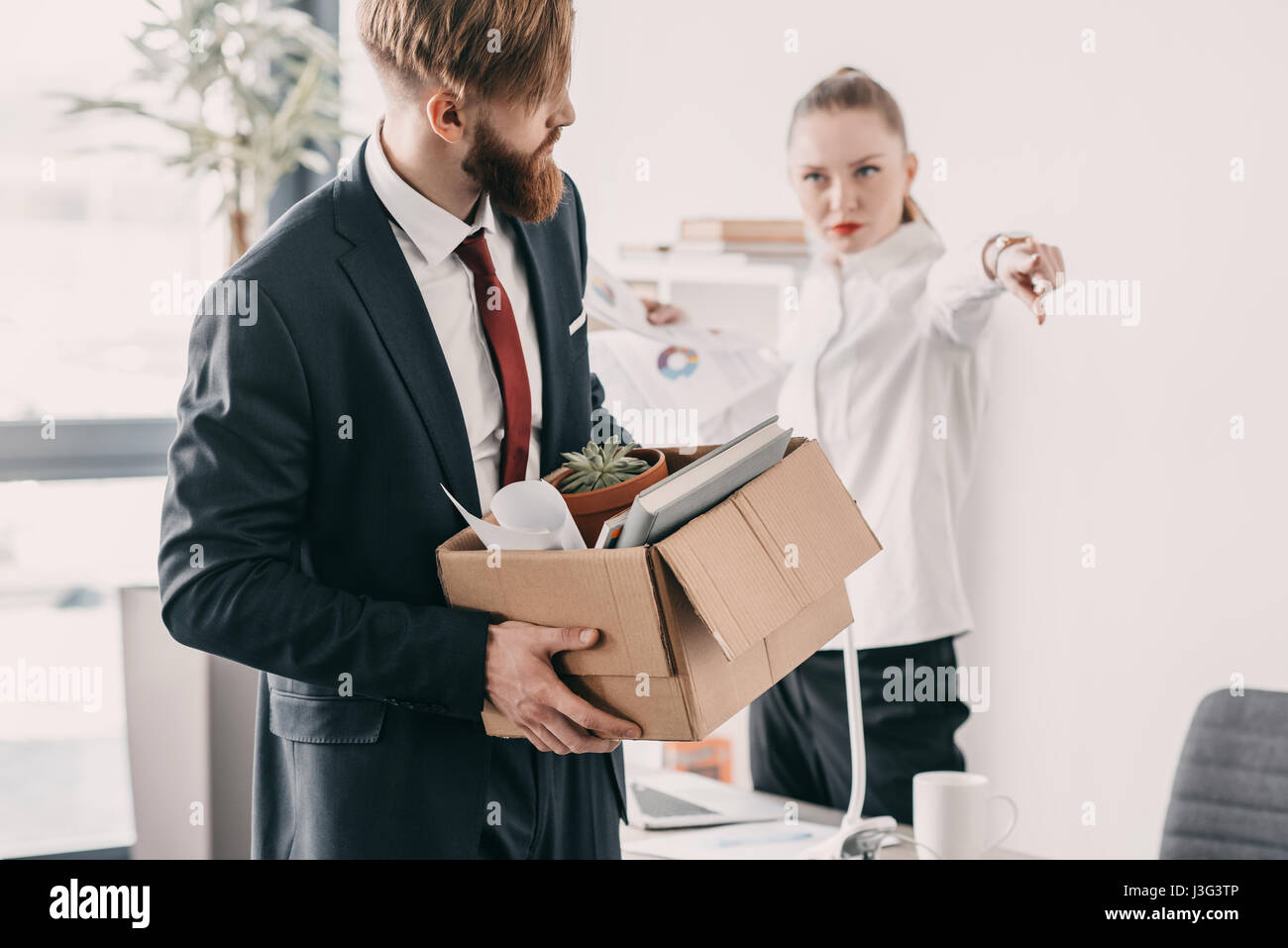 Young upset fired businessman with cardboard box and boss in office - Stock Image