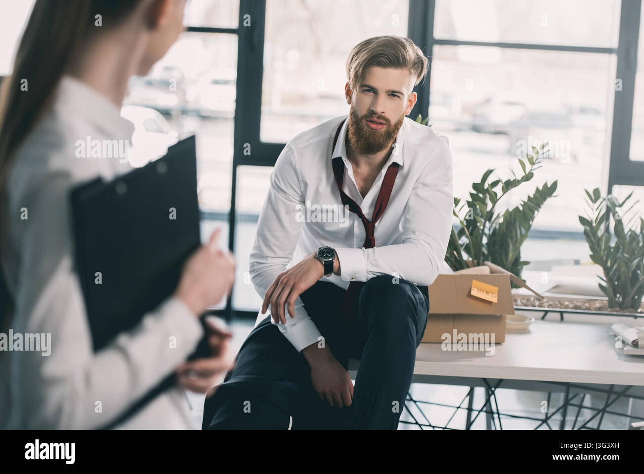 Young upset fired businessman with cardboard box in office - Stock Image