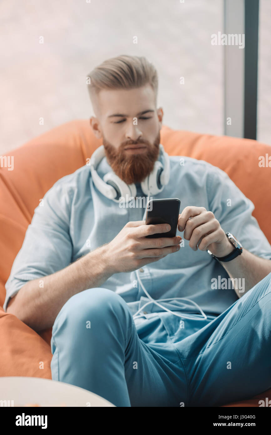Young man with headphones sitting in bean bag chair and using smartphone - Stock Image