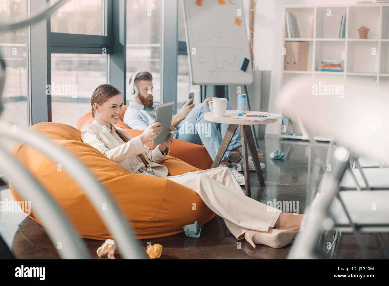 Young business people sitting in bean bag chairs and using devices - Stock Image