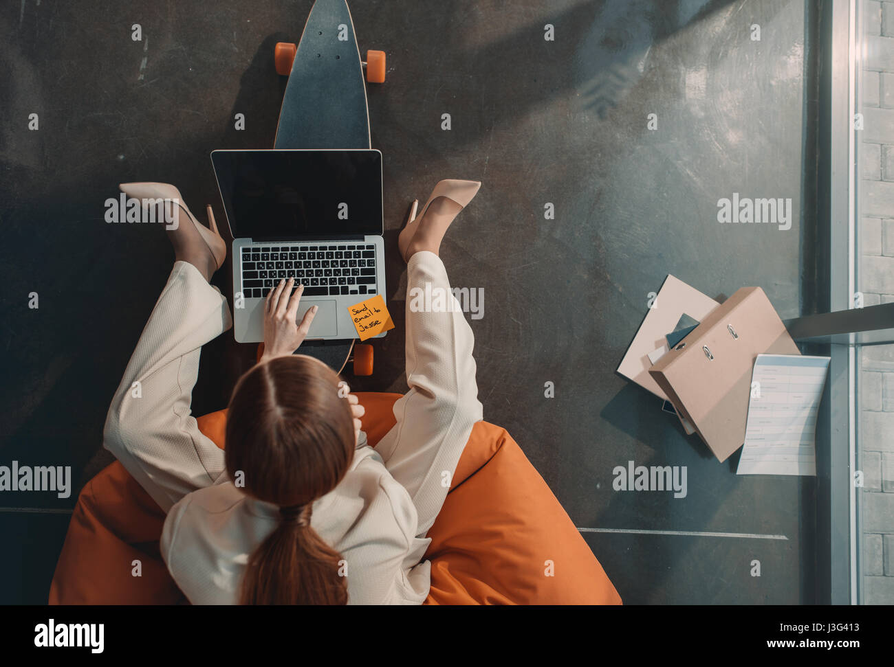Overhead view of young businesswoman sitting in bean bag chair and using laptop - Stock Image