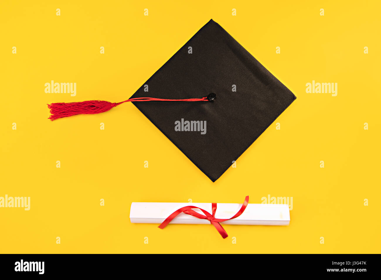 Top view of graduation mortarboard and diploma on yellow background, education concept - Stock Image