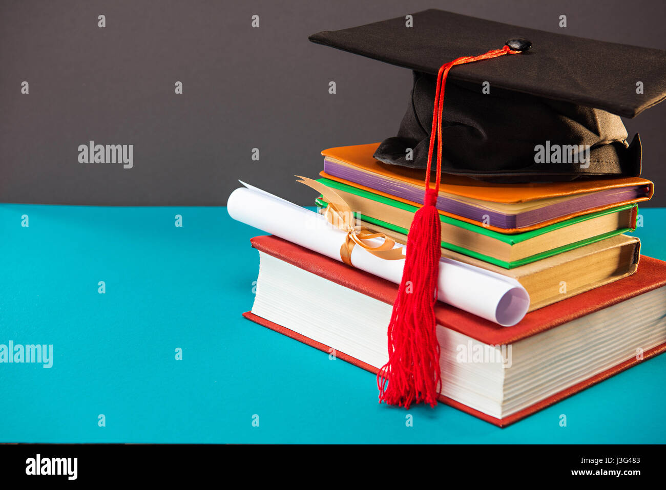 books, diploma and graduation cap with tassel on blue with copy space, education concept - Stock Image