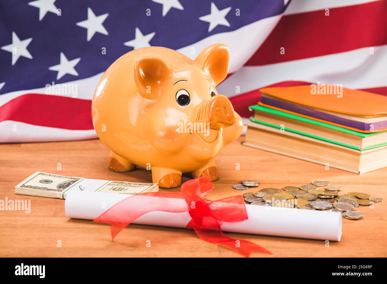 diploma and piggy bank with coins and dollars usa flag behind, education concept - Stock Image