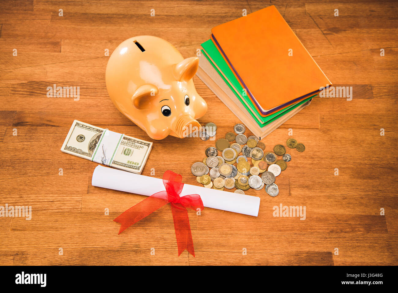 diploma, books and piggy bank with coins and dollars on wooden tabletop, education concept - Stock Image