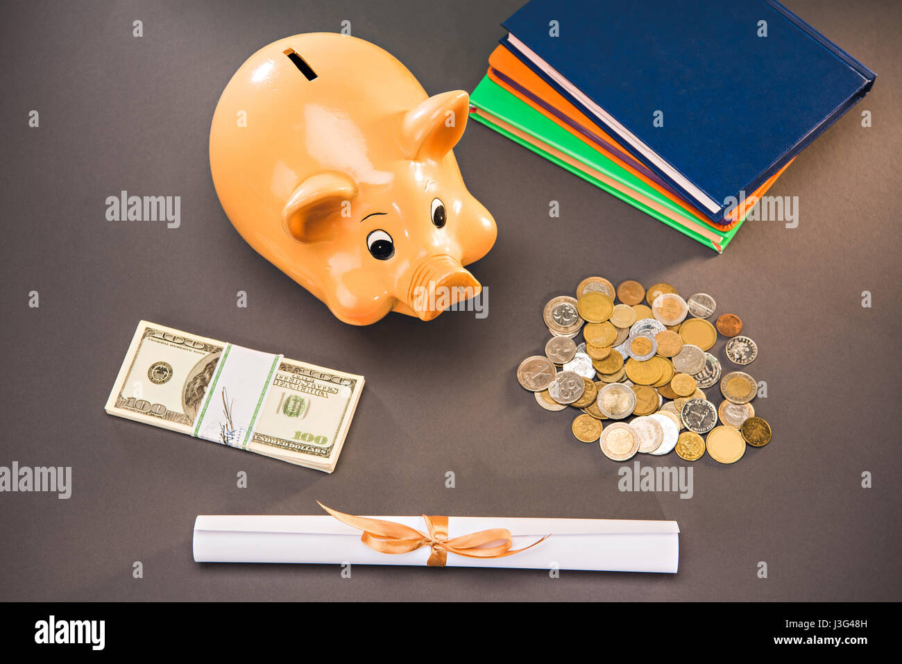 diploma, books and piggy bank with coins and dollars on grey, education concept - Stock Image