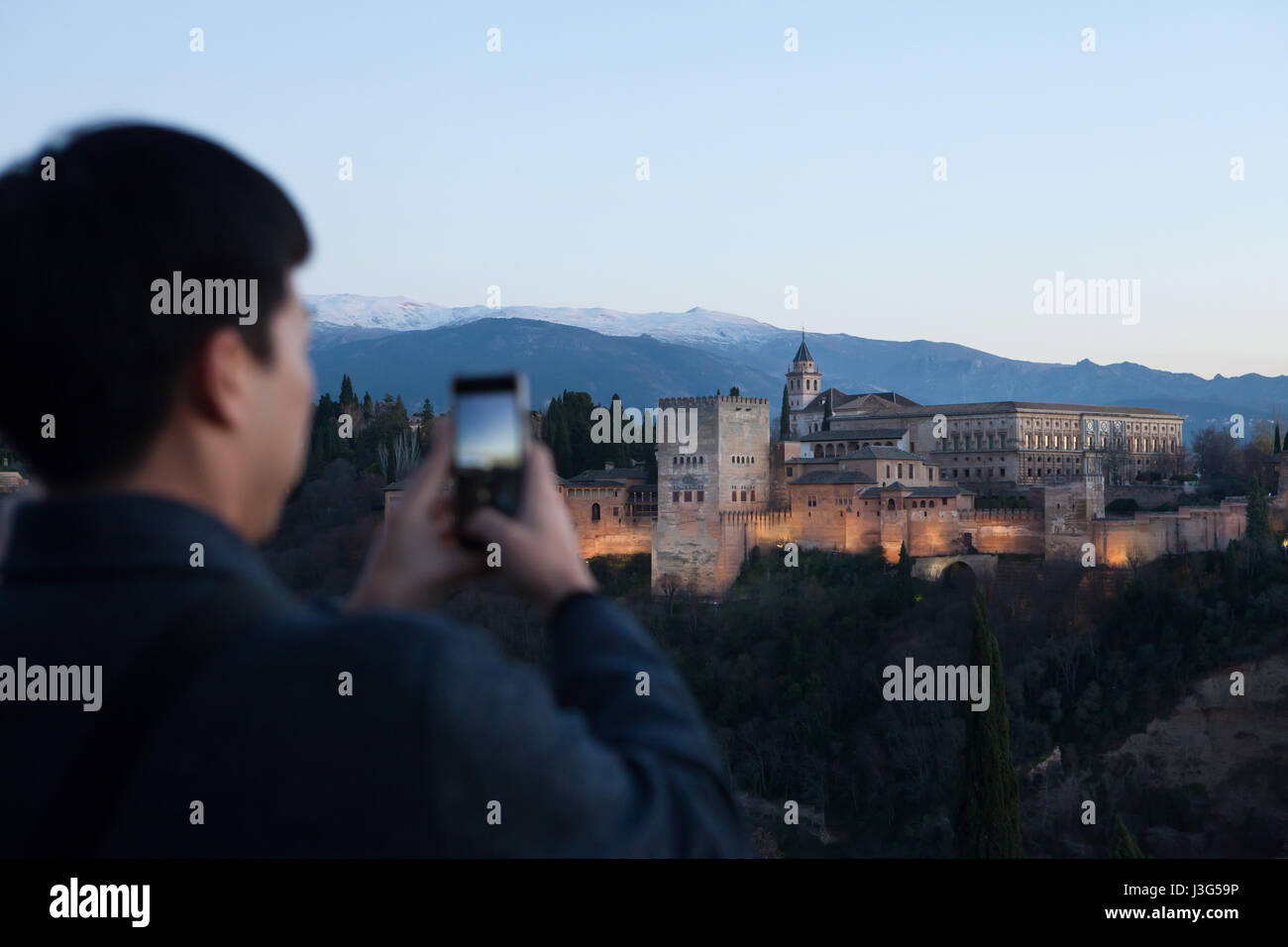Asian tourist uses his smartphone to photograph the Alhambra Palace from the Mirador de San Nicolas in El Albayzin Stock Photo