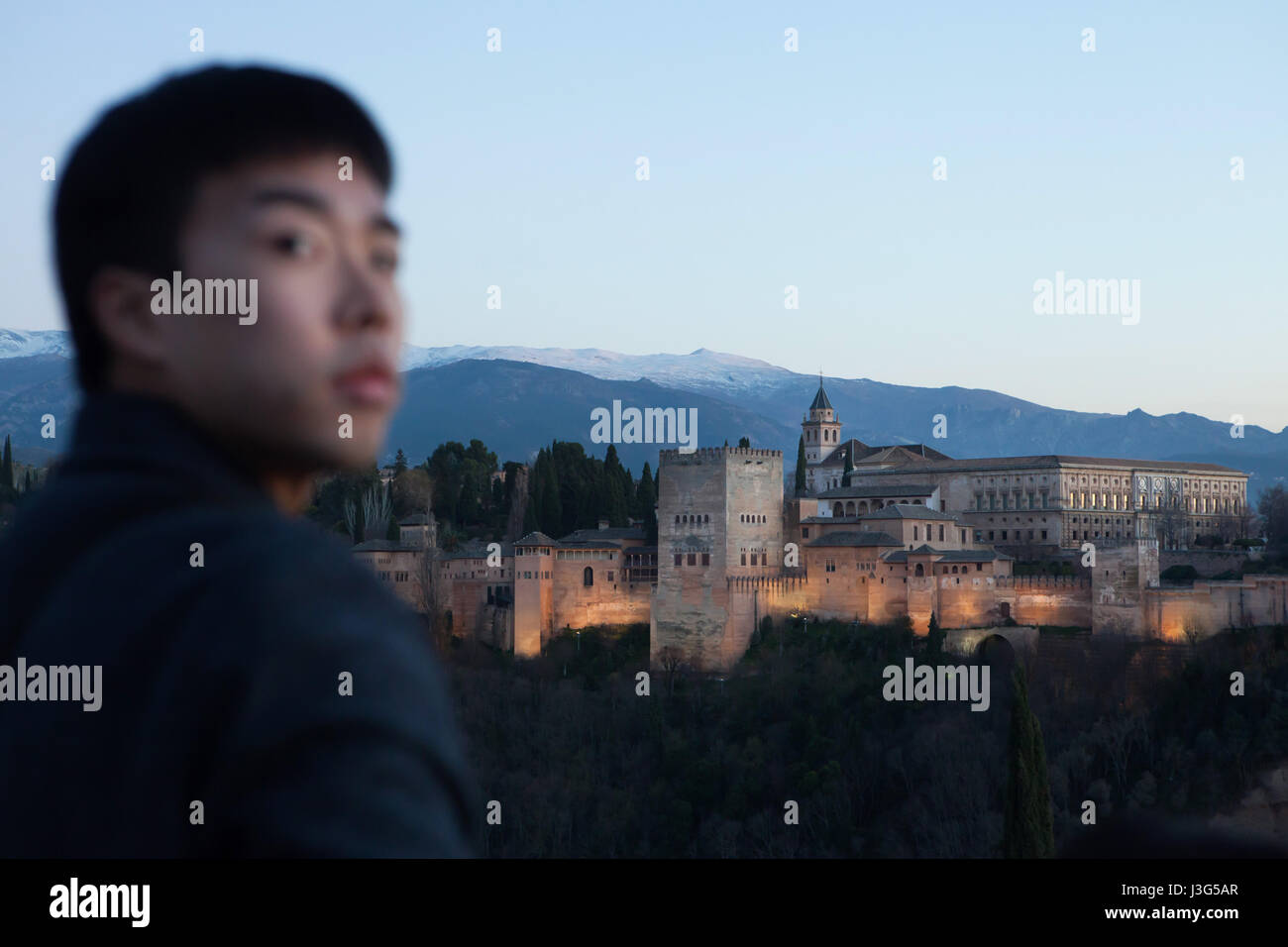 Asian tourist in front of the Alhambra Palace pictured from the Mirador de San Nicolas in El Albayzin district in Stock Photo