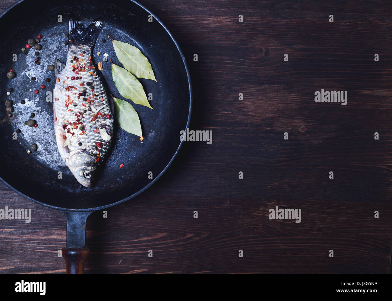 Carp fish in spices on a black cast-iron frying pan, empty space on the right Stock Photo