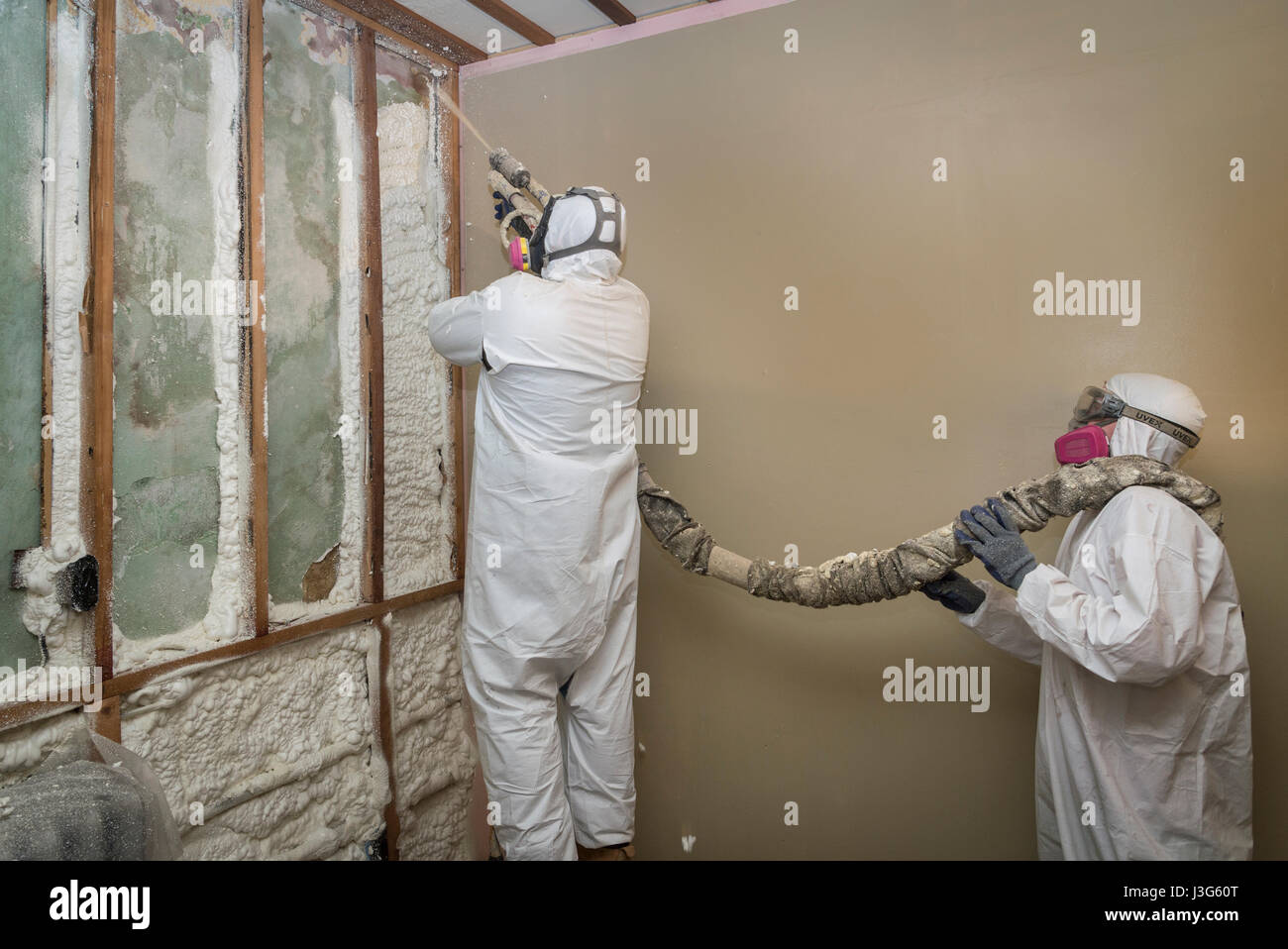 Workers Spraying Open Cell Foam Insulation On Interior Walls Of Home - Stock Image