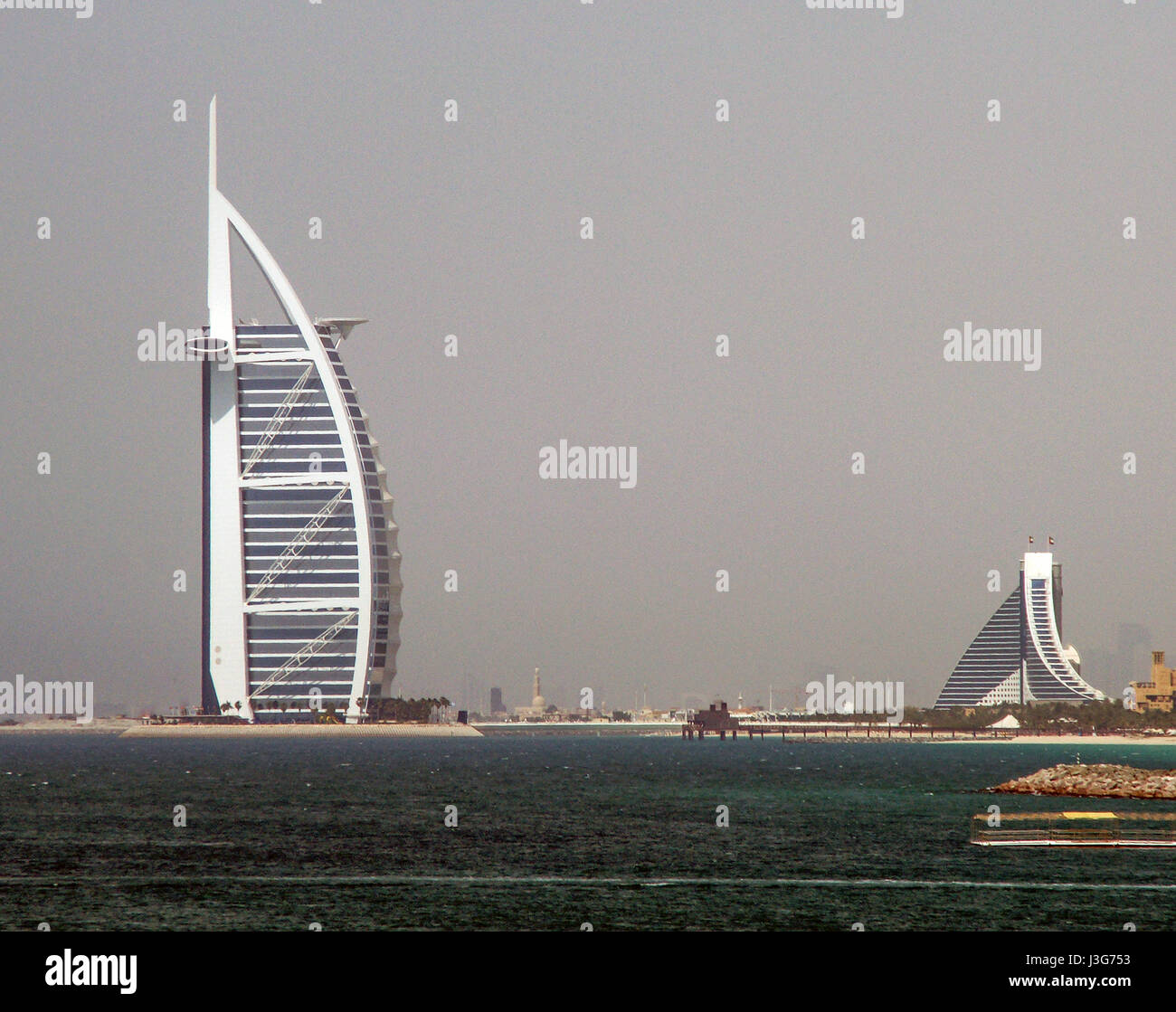 The famous Burj Al Arab hotel (left) and Jumeirah Beach Hotel (right) as seen from the sea. The haze is so heavy - Stock Image