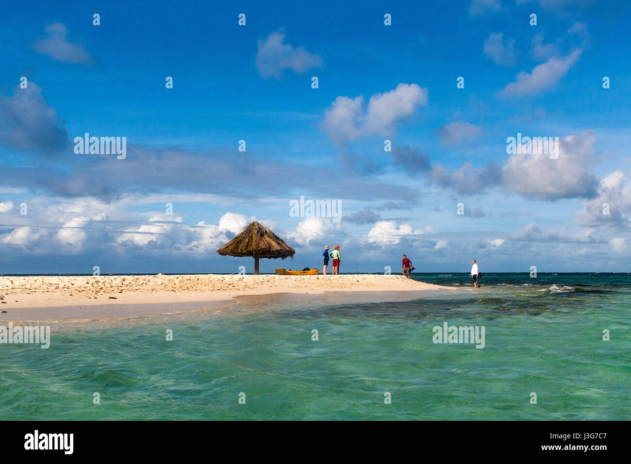 Group of Visitors arriving on Tiny Mopian Island: Solitary Parasol and Distant Islands: Mopian Island, Saint Vincent - Stock Image