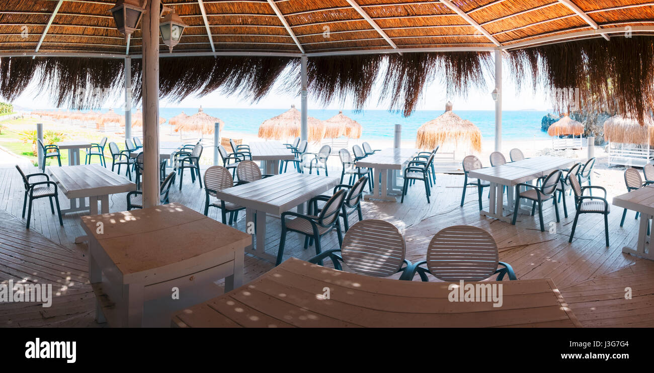 Summer restaurant on beach. Breathtaking view on mediterranean sea. White wooden furniture and cane roof - Stock Image